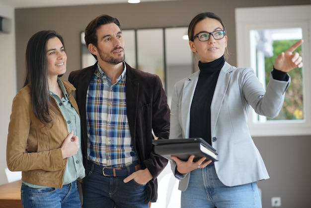 Real estate agent showing modern house to attractive couple Premium Photo