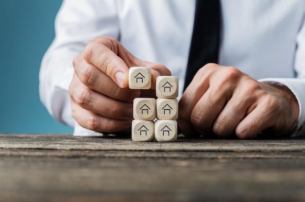 Агент по недвижимости укладывает деревянные кубики с формой дома на концептуальном изображении. Premium Фотографии
