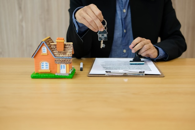 Real estate agent with house key stamping approved on mortgage loan contract agreement document Premium Photo