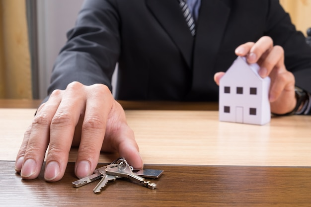 Real estate agent with house model and keys Free Photo