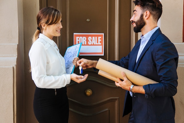 Real estate agent and woman interchanging keys Free Photo