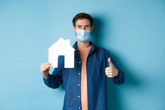 부동산 및 Covid 개념. 종이 집 컷 아웃 및 엄지 손가락 업을 보여주는 얼굴 마스크에 젊은 남자, 기관 추천, 파란색 배경에 서. 프리미엄 사진