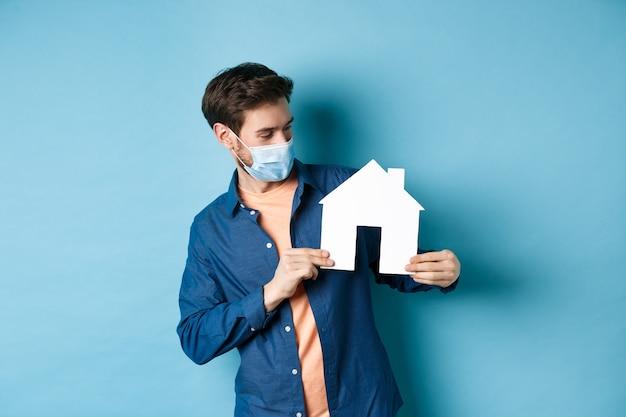 부동산 및 검역 개념. 파란색 배경에 서 종이 집 컷 아웃에 호기심 찾고 의료 마스크에 젊은 백인 남자. 프리미엄 사진