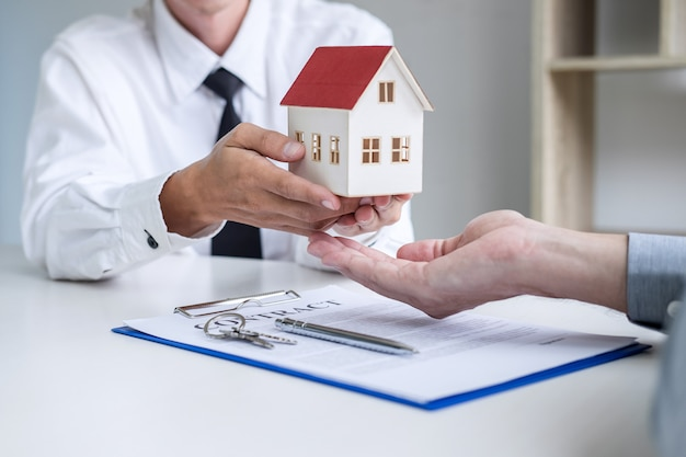Real estate broker agent presenting and consult to customer to decision making sign insurance Premium Photo