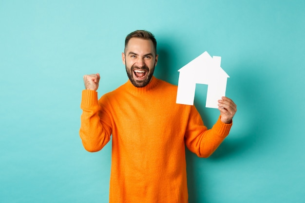 Real estate concept. excited man saying yes, showing paper house maket and looking satisfied Free Photo
