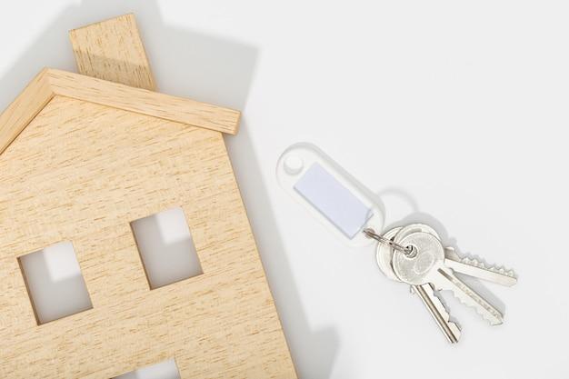 Концепция недвижимости. значок дома с ключами на белом фоне. макет. копировать пространство вид сверху Premium Фотографии