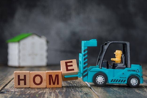 Real estate concept with model house on wooden table side view. forklift carrying letter block e to inscription home. Free Photo