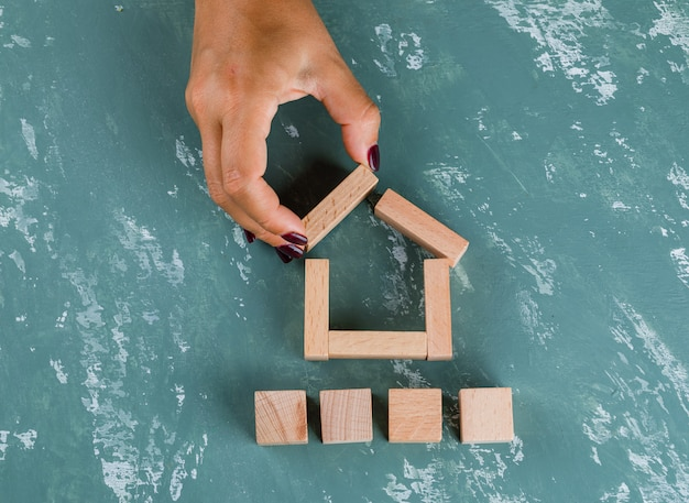 Real estate concept with wooden blocks flat lay. woman making house model. Free Photo