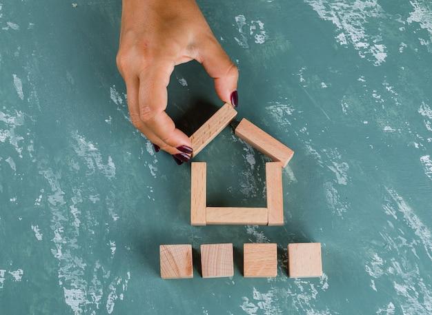 Концепция недвижимости с деревянными блоками плоской планировки. женщина делает модель дома. Бесплатные Фотографии