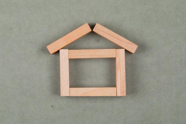 Концепция недвижимости с деревянными блоками на сером фоне плоской планировки. Бесплатные Фотографии