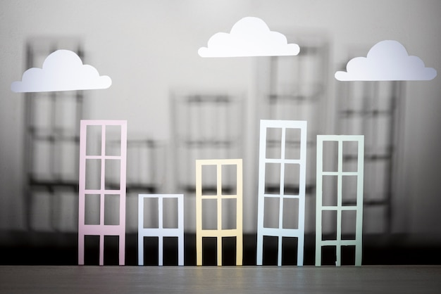 Real estate design with paper buildings and clouds Free Photo