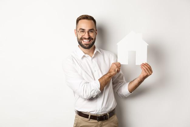 부동산. 잘 생긴 남자 집 모델을 보여주는 미소, 브로커 보여주는 아파트, 서 무료 사진