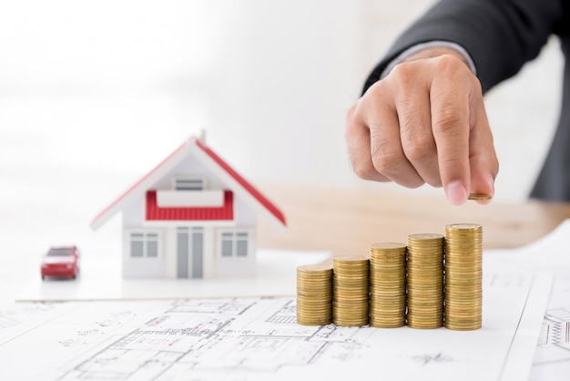Real-estate investor projecting profit growth of housing development plan using coins Premium Photo
