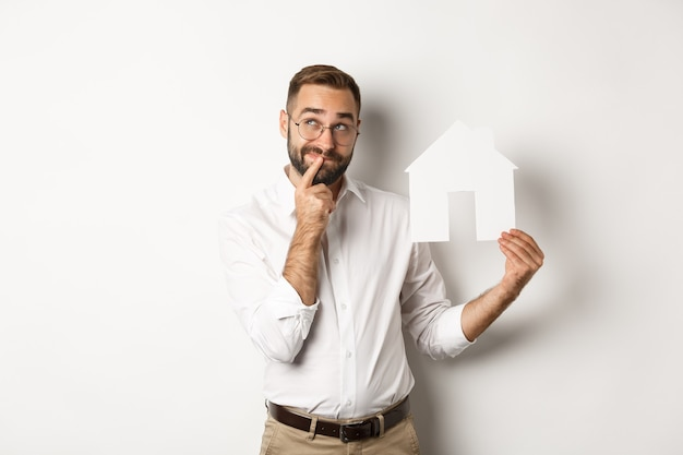 Недвижимость. человек думает во время поиска квартиры, держа модель бумажного дома, стоя Бесплатные Фотографии
