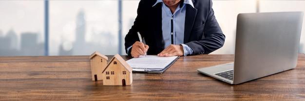Недвижимость, собственность и домовладелец подписывают договор по концепции банковского агентства, модель небольшого деревянного дома на офисном столе с подписанием на бумаге договора аренды на аренду вышеупомянутой резиденции Premium Фотографии