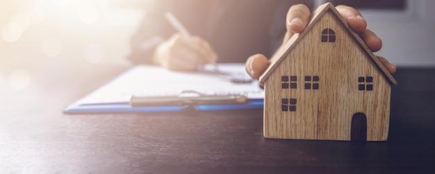 不動産、不動産、住宅所有者が契約の概念に署名、女性のバイヤーの手でオフィスのテーブルに小さな木造住宅モデルが上記の住宅を賃貸する賃貸契約書にサイン Premium写真