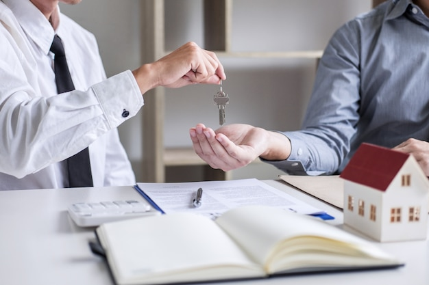 Real estate sales manager giving keys to customer after signing rental lease contract of sale purchase agreement Premium Photo