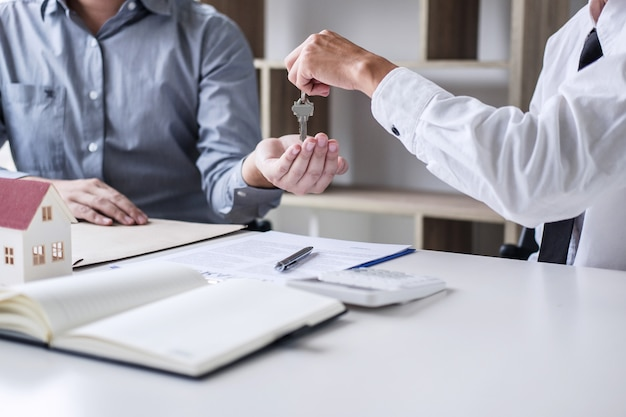 Real estate sales manager giving keys to customer after signing rental lease contract Premium Photo