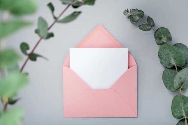 실제 사진. 유칼립투스 분기와 핑크 봉투 광장 초대 카드 모형. 복사 공간, 밝은 회색 배경으로 상위 뷰. 브랜딩 및 광고용 템플릿 프리미엄 사진