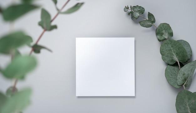 本物の写真。ユーカリの枝が付いている正方形の招待状のモックアップ。コピースペース、明るい灰色の背景の上面図。ブランディングと広告のためのテンプレート Premium写真