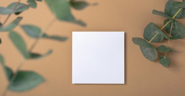 本物の写真。ユーカリの枝が付いた正方形の招待状のモックアップ。コピースペース、パステルベージュの背景を持つ上面図。ブランディングと広告のためのテンプレート。 Premium写真
