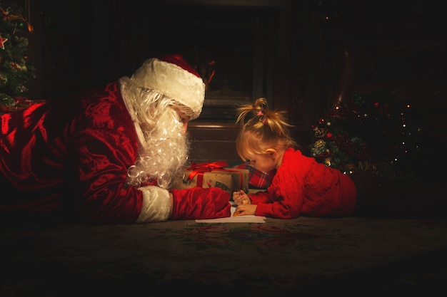 Real santa claus is playing with children near the christmas tree. Premium Photo