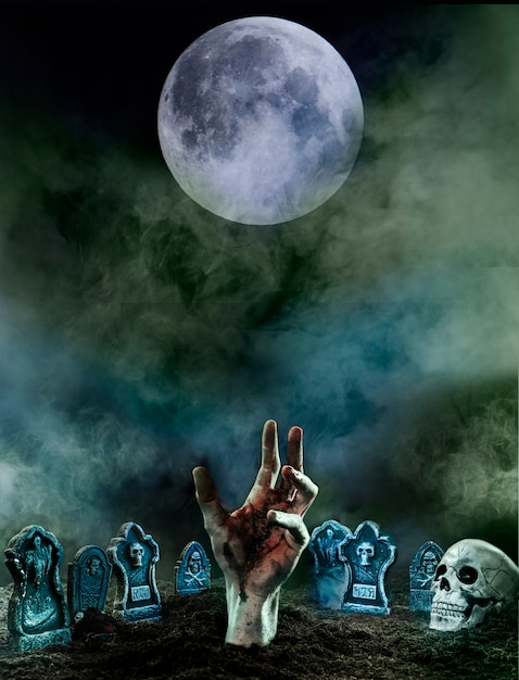 Realistic hand in a graveyard surrounded by tombstones Free Photo