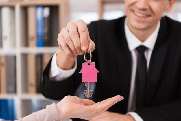 Realtor gives woman keys with keychain in form of house Premium Photo