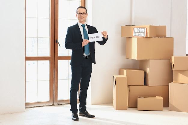 Realtor holding  new apartment with cardboard boxes. Premium Photo