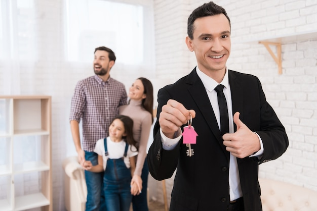 Realtor in suit holds keys with key fob in form of house. Premium Photo