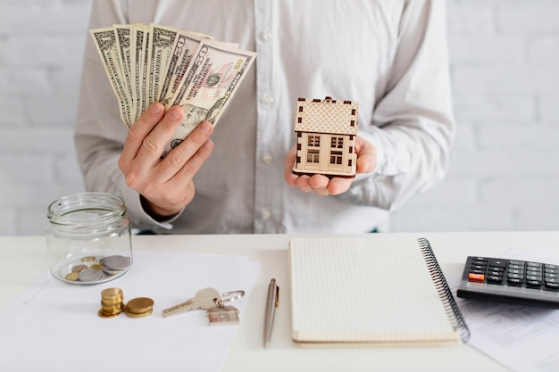 Realtor with money and wooden house Free Photo