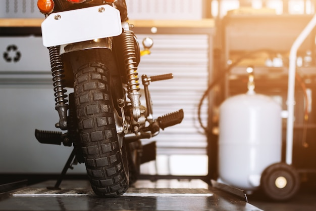 The rear of the classic motorcycles standing in repair shop Premium Photo