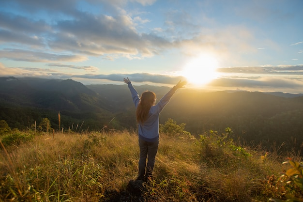 Rear of happy woman stand on top mountain looking view with sunrise and mist at doi langka luang, chiang rai province. soft focus. Premium Photo