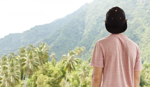 夏休みに彼の旅行中に自由で平和なスナップバックを身に着けている若い白人旅行者の後姿 無料写真