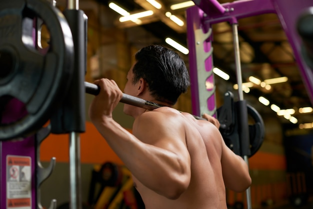 Rear side view of topless athlete lifting weight in the gym Free Photo