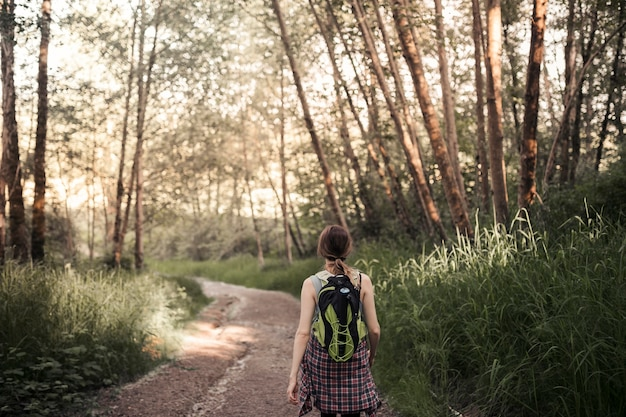 Rear vie of woman walking on the dirt road in the forest Free Photo