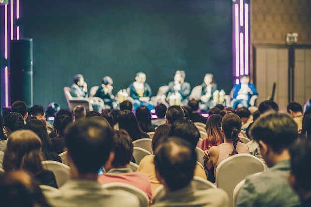 Rear view of asian audience joining and listening group of speaker talking on the stage Premium Photo