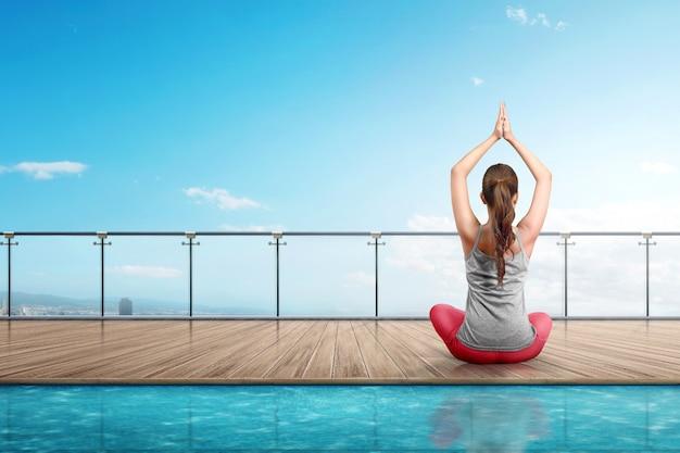 Rear view asian woman doing yoga on wooden floor Premium Photo