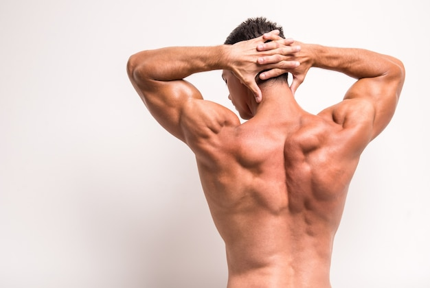 Rear view of athletic man is showing muscles. Premium Photo