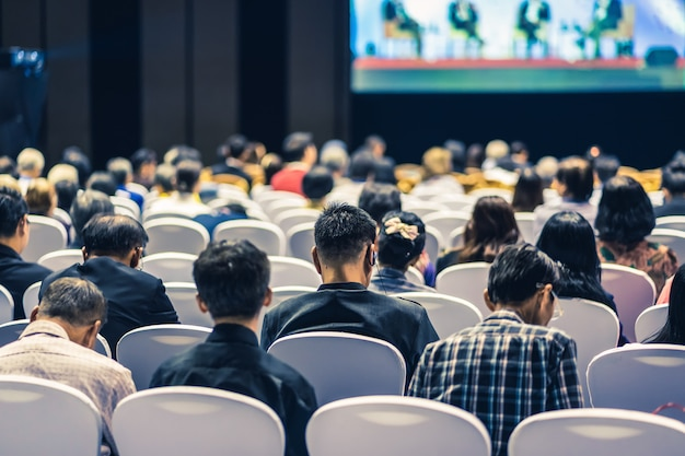 Rear view of audience listening speakers on the stage in the conference hall or seminar meeting, business and education about investment concept Premium Photo