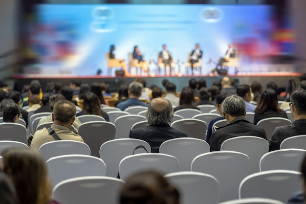 Rear view of audience listening speakers on the stage in the conference hall or seminar meeting Premium Photo