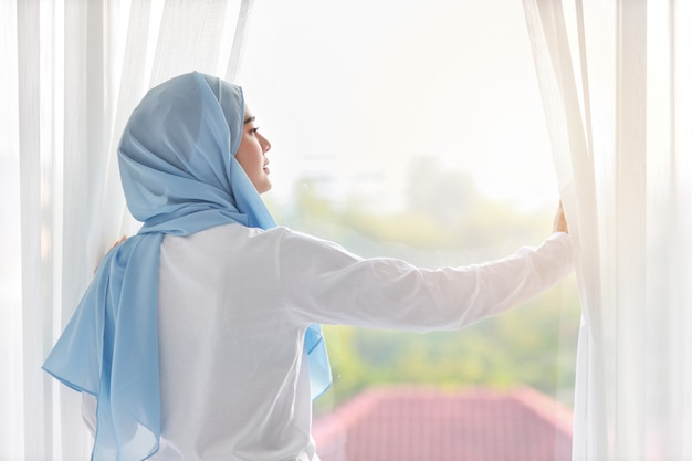 Rear view beautiful asian muslim woman wearing white sleepwear, stretching her arms after getting up in the morning at sunrise. cute young girl with blue hijab standing and relaxing while looking away Premium Photo