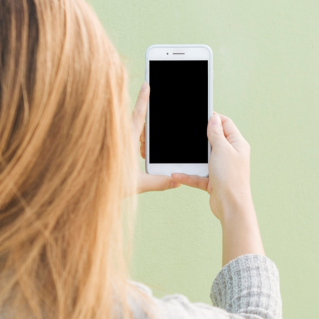 Rear view of a blonde young woman holding mobile phone against mint green backdrop Free Photo