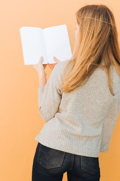 Rear view of a blonde young woman holding white book in hand against peach backdrop Free Photo