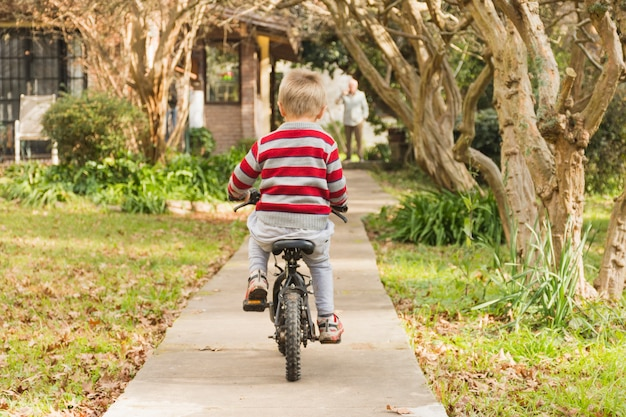 Rear view of boy cycling in front yard Premium Photo