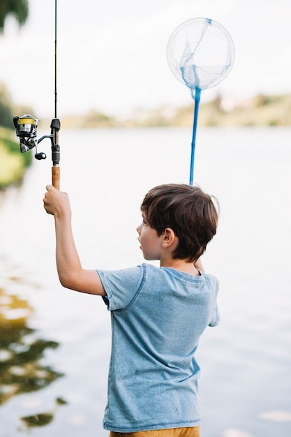 Rear view of boy raising hands holding fishing rod and net in front of lake Free Photo