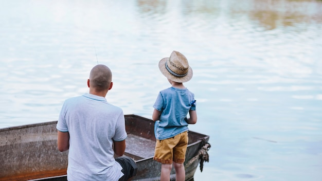 Rear view of boy with his father fishing Free Photo