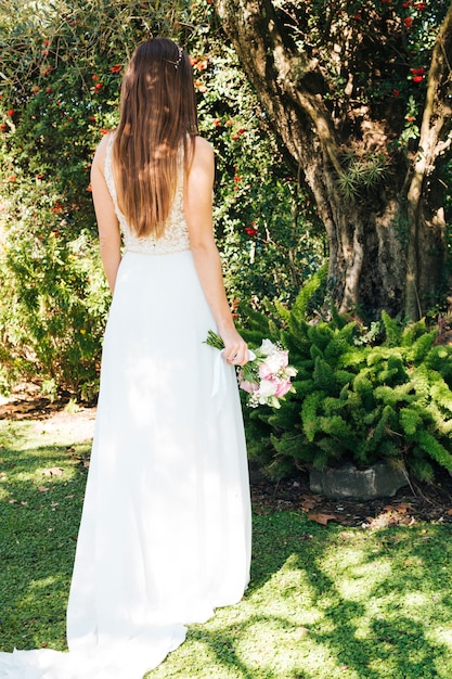Rear view of a bride holding flower bouquet in hand standing in the park Free Photo