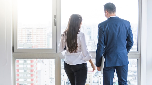 Rear view of businessman and businesswoman looking out of window Free Photo