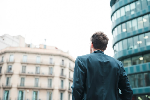 Rear view of a businessman looking at corporate building in the city Free Photo